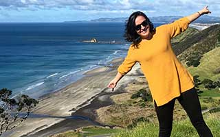 Charlie in a yellow top and black trousers standing on top a hill in New Zealand